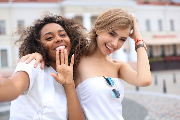 Молодые улыбающиеся хипстерские женщины в летней одежде, позирующие на улице. женщина, показывающая положительные эмоции лица.
