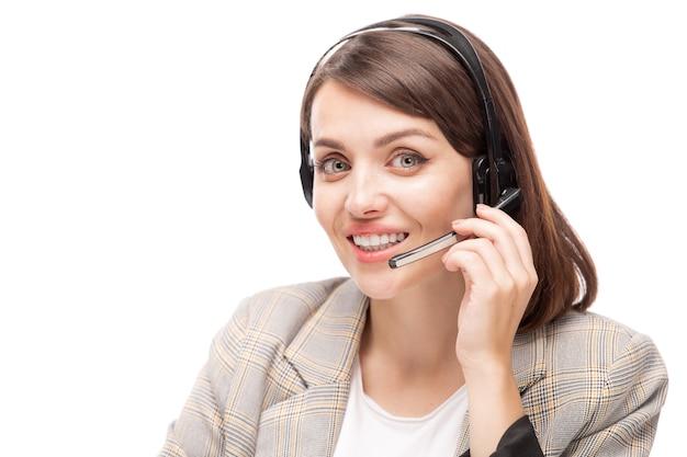 Молодой улыбающийся консультант горячей линии в гарнитуре отвечает на вопрос клиента, глядя на вас