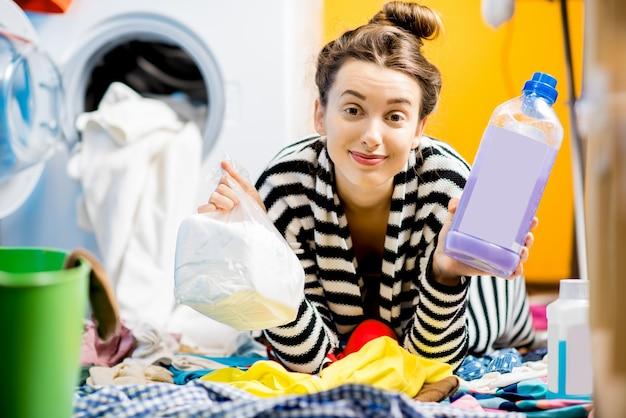 Молодая улыбающаяся домохозяйка держит бутылку с моющим средством и порошком, сидя на полу возле стиральной машины дома