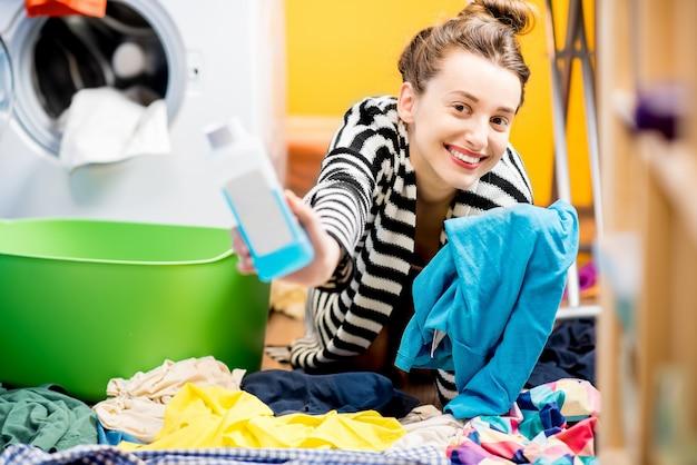 Молодая улыбающаяся домохозяйка держит бутылку с моющим средством и футболку, сидя на полу возле стиральной машины дома
