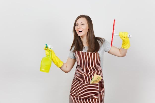 黄色の手袋、縞模様のエプロン、分離されたポケットの雑巾を掃除する若い笑顔の主婦