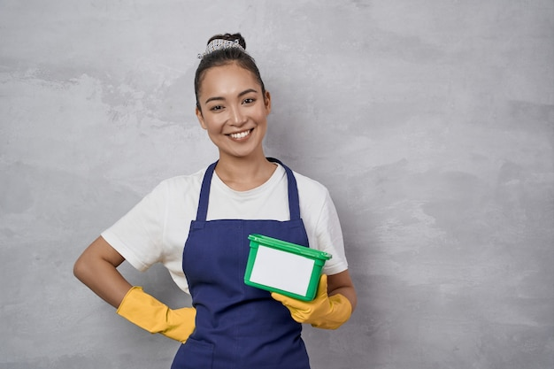Young smiling housewife or maid woman in uniform and yellow rubber gloves holding green plastic