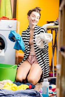 Молодая улыбающаяся домохозяйка сидит на полу в яркой одежде возле стиральной машины дома