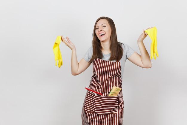 Giovane casalinga sorridente in grembiule a strisce con uno straccio per la pulizia in tasca isolata