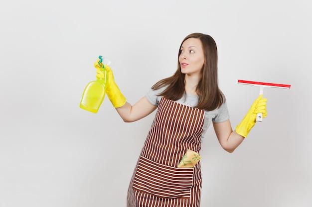 Giovane casalinga sorridente in guanti gialli, grembiule a strisce, straccio per la pulizia in tasca isolata