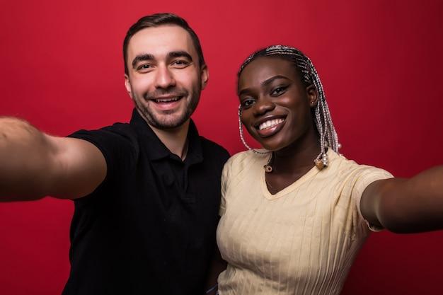 若い笑顔の異人種間のカップル、コーカサス人の男と赤の背景に携帯電話でselfieを取ってアフリカの女性