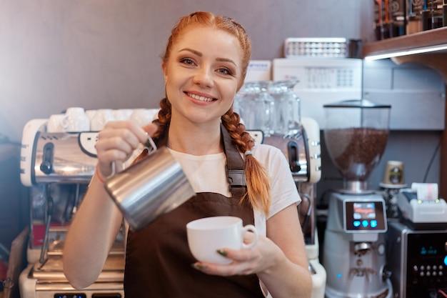 Молодая улыбающаяся леди-бариста в коричневом фартуке готовит и заказывает кофе, стоя у стойки кафе с кофемашиной на фоне