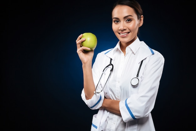 Young smiling lady doctor holding apple and looking