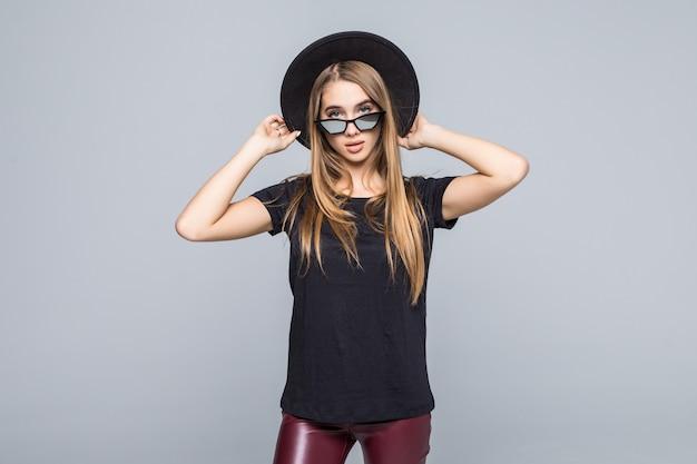 黒い帽子、黒いtシャツ、灰色の背景に分離された暗いズボンで着飾った鮮やかなサングラスの若い笑顔の女性