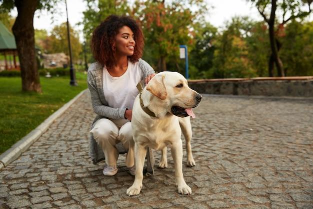座っていると公園で犬を抱いてカジュアルな服装の若い笑顔の女性