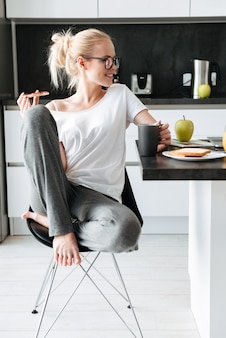 Young smiling lady looking aside while have breakfast in kitchen