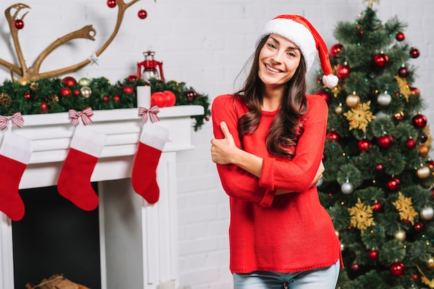 Young smiling lady near christmas tree