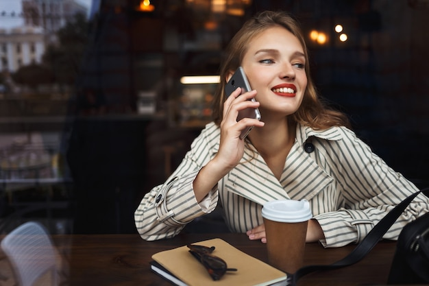 Young smiling lady in striped trench coat talking on cellphone happily
