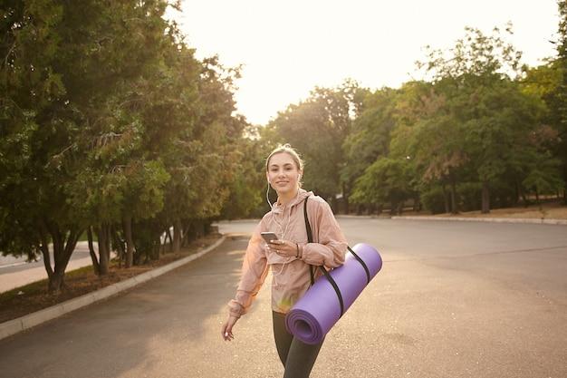 Giovane donna sorridente che cammina dopo lo yoga al parco e chiacchiera con un amico spiritoso, tiene in mano lo smartphone, ascolta musica in cuffia, si sente benissimo.
