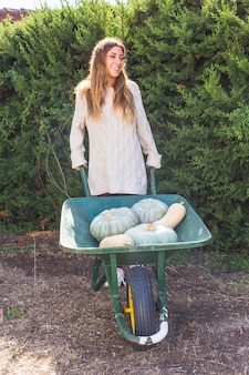 Young smiling lady with fresh vegetables in utility cart