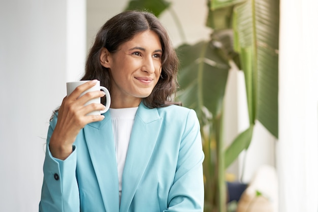 Молодая улыбающаяся латинская деловая женщина довольна хорошо выполненной работой, расслабляясь с утренним кофе
