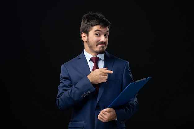 Young smiling male office worker in suit holding and pointing documents on isolated dark wall