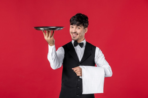 Giovane cameriere maschio sorridente in uniforme con farfalla sul collo e vassoio alzante che tiene asciugamano su sfondo rosso