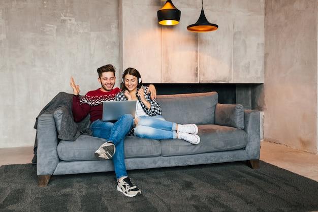Молодой улыбающийся мужчина и женщина, сидящие дома зимой, глядя в ноутбук с счастливым выражением лица, используя интернет, пара на досуге вместе, положительные эмоции, свидания