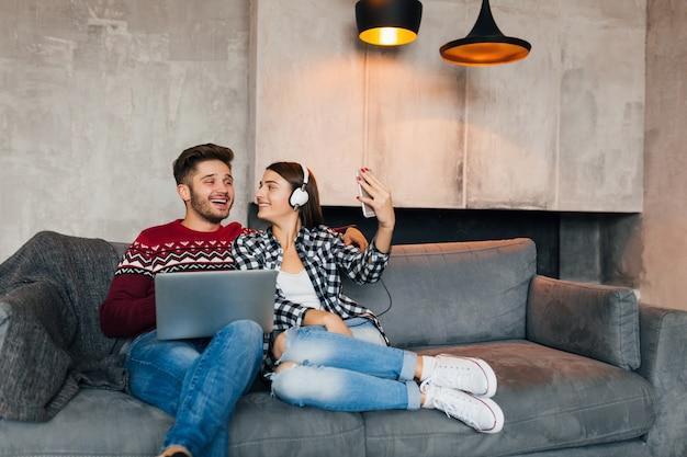 Молодой улыбающийся мужчина и женщина сидят дома зимой с ноутбуком, слушают наушники, пара вместе проводят свободное время, делая селфи-фото на камеру смартфона, счастливы, позитивны, свидания, смеются