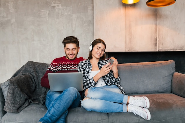 若い笑顔の男と女の冬の家に座って、ラップトップに取り組んで、スマートフォンを持ち、ヘッドフォンを聞いて、オンラインで時間を過ごす余暇のカップル、フリーランサー、デート