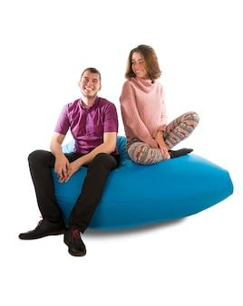 リビングルームまたは白で隔離された他の部屋の青いお手玉のソファに座っている若い笑顔の男性と女性