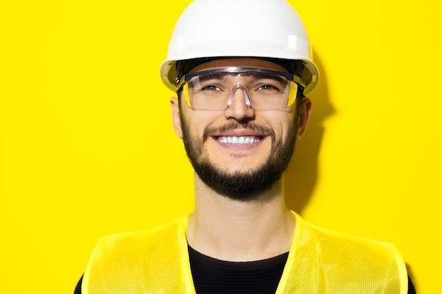 Молодой улыбающийся человек-архитектор, инженер-строитель в защитных очках, жестком шлеме и светоотражающей куртке на желтой стене