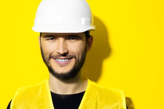 Молодой улыбающийся человек-архитектор, инженер-строитель в жестком строительном защитном шлеме и светоотражающей куртке на желтой стене
