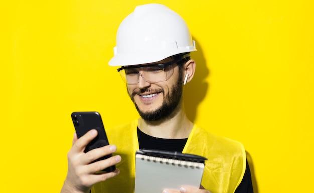 Молодой улыбающийся человек архитектор, инженер-строитель, в белом строительном защитном шлеме, очках и куртке. используя смартфон и беспроводные наушники, изолированные на желтой стене.
