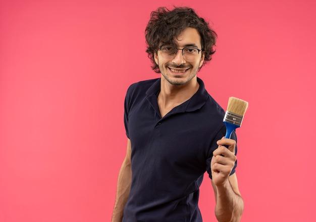 Il giovane uomo sorridente in camicia nera con vetri ottici tiene il pennello e sembra isolato sulla parete rosa