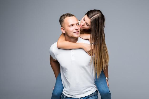 Giovane uomo sorridente che trasportano fidanzata sulla schiena in studio