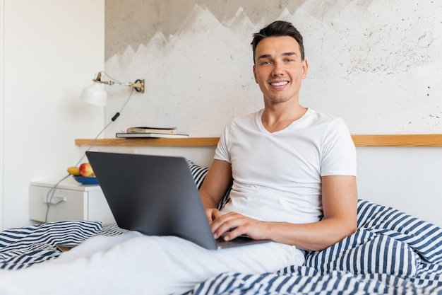 Young smiling man in casual pajamas outfit sitting in bed in morning working on laptop