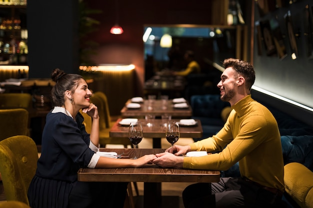 Young smiling man and cheerful woman holding hands at table with glasses of wine in restaurant