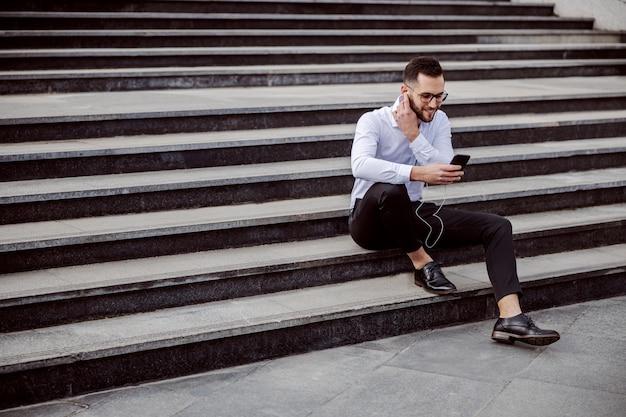 屋外の階段に座ってエレガントな服を着て、耳にイヤホンを入れて、スマートフォンを使用して若い笑顔の男。