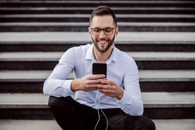 若い笑顔の男はエレガントな服を着て、耳にイヤホンが付いている階段の上に座って、ソーシャルメディアのメッセージをチェックするためにスマートフォンを使用しています。