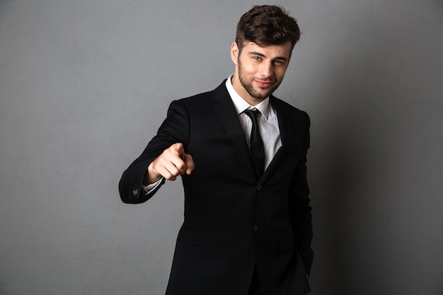 Young smiling man in formal wear pointing with finger on you,