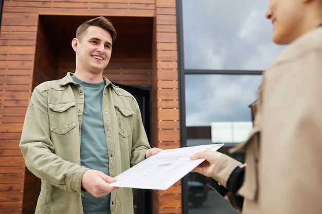 Молодой улыбающийся человек получает письмо от почтальона, стоя на открытом воздухе