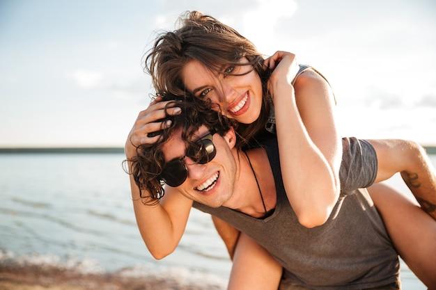 Молодой улыбающийся человек, совершающий поездку на спине подруге на берегу океана