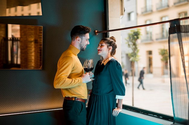 Young smiling man and happy woman with glasses of wine near window
