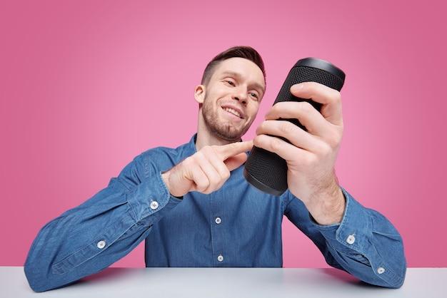 Молодой улыбающийся человек, держащий черную портативную колонку цилиндрической формы, выбирая радиостанцию или музыку для прослушивания