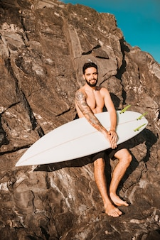 Young smiling man holding surf board near stones