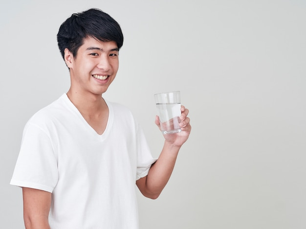 Young smiling man holding water glass