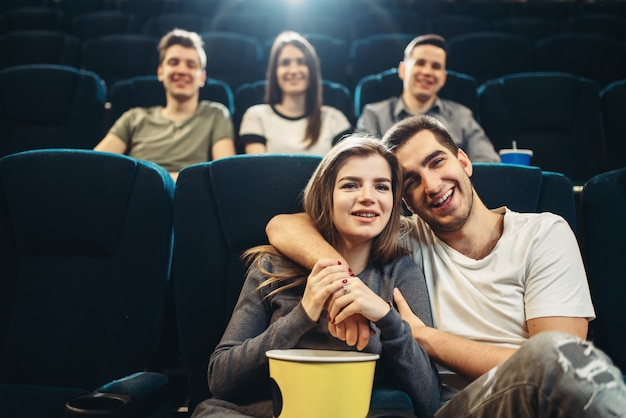 Young smiling man hugs his woman in cinema. showtime, entertainment industry, movie watching