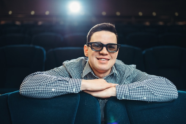 Молодой улыбающийся человек в очках 3d смотрит фильм в кино. showtime, индустрия развлечений