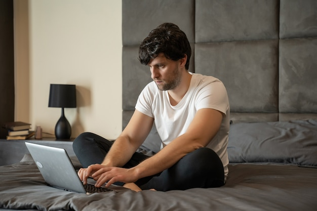 Молодой улыбающийся человек в белой футболке сидит в постели, работая над ноутбуком, фрилансером дома