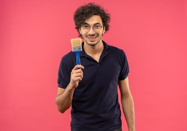 光学メガネと黒のシャツの若い笑顔の男はブラシを保持し、ピンクの壁に孤立して見える