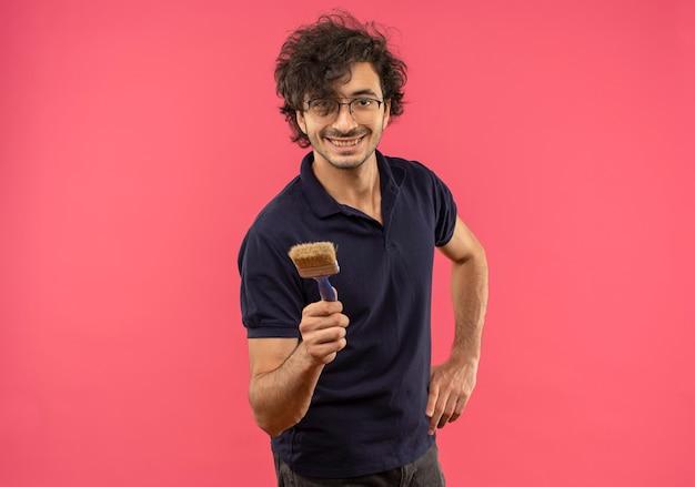 Молодой улыбающийся человек в черной рубашке с оптическими очками держит кисть и кладет руку на талию, изолированную на розовой стене