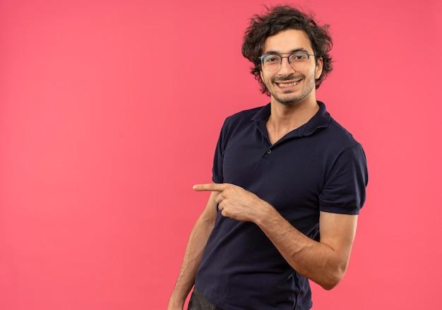 분홍색 벽에 고립 된 측면에서 광학 안경 포인트와 검은 셔츠에 젊은 웃는 남자