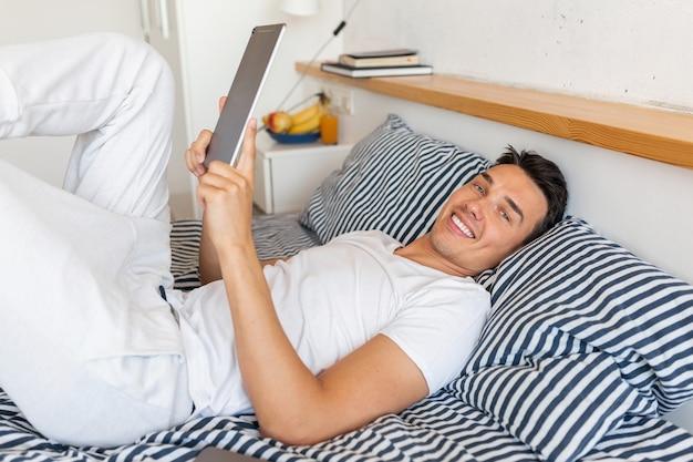 タブレットを保持している朝のベッドに座っているカジュアルなパジャマの衣装で若い笑顔の男