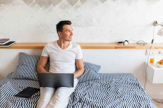 Молодой улыбающийся человек в повседневной пижамной одежде сидит в постели утром, работая на ноутбуке, фрилансер дома